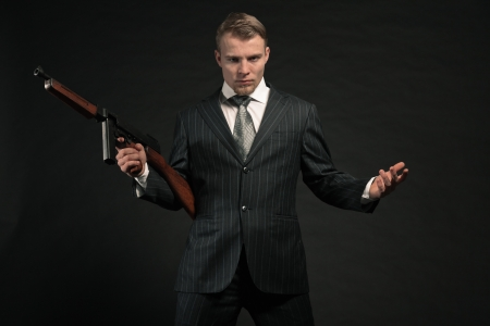Man in suit shooting with rifle. Studio shot against black. photo
