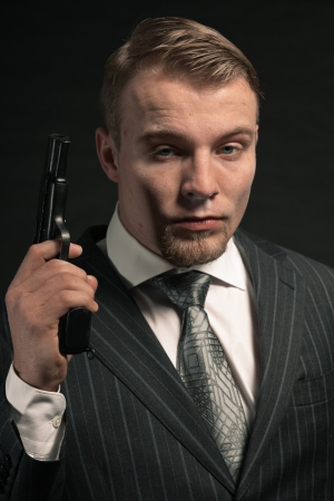 Mafia man in suit with cocaine and gun. Studio shot. Stock Photo - 17802600