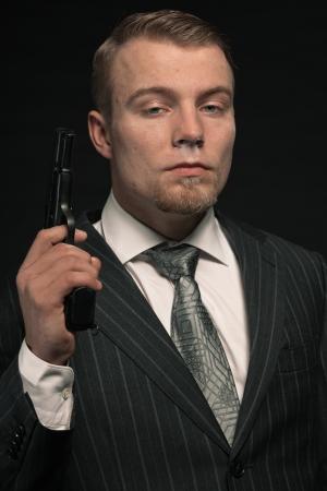 man holding gun: Mafia man in suit with cocaine and gun. Studio shot.