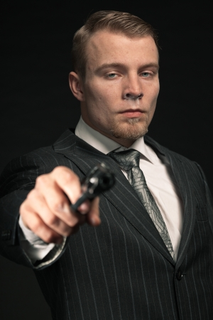 Mafia man in suit with cocaine and gun. Studio shot. photo