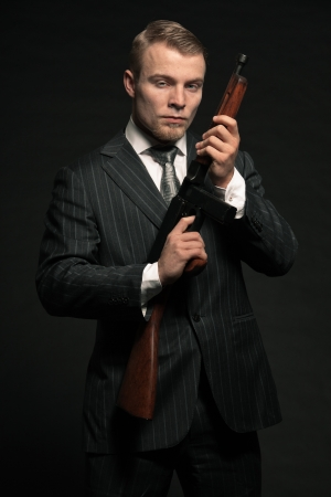 Mafia man in suit with cocaine and rifle. Studio shot. photo