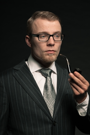 Fashion man in suit with glasses and pipe. Studio shot. photo