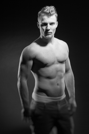 Muscled fitness man. Black and white studio shot. photo