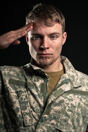 salutes: Military young man salutes. Studio portrait.