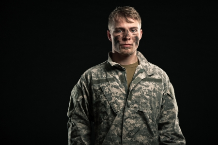 fatigues: Military young man with camouflage on face. Studio shot.