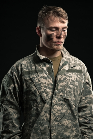 Military young man with camouflage on face. Studio shot. photo