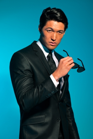 Asian man in suit with sunglasses. Summer fashion. Studio. photo