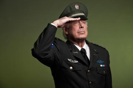 US military general wearing cap. Salutation. Studio portrait. photo