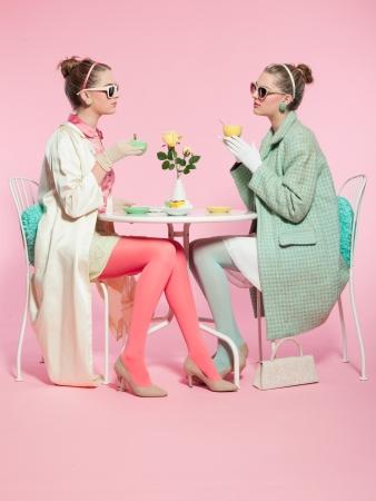 Two girls blonde hair fifties fashion style drinking tea