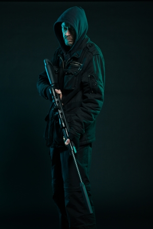 one armed: Sniper with beard in black holding gun. Studio shot.