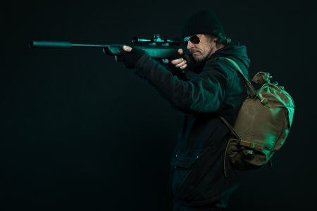 Sniper with beard in black holding gun. Studio shot. photo