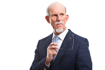 Serious well dressed senior man holding glasses. Isolated. photo