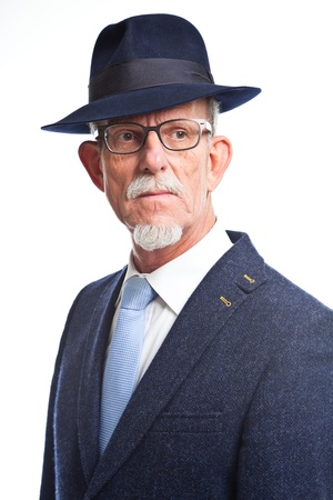 Serious well dressed senior man with hat. Isolated. photo
