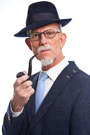 Well dressed senior man with glasses smoking pipe. Isolated. photo