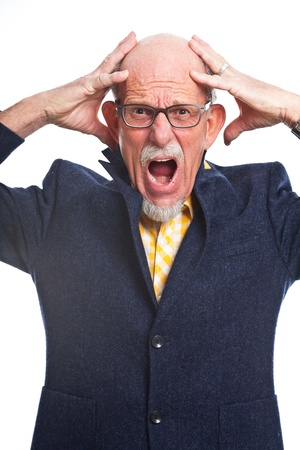 Angry well dressed senior man with glasses. Isolated. photo