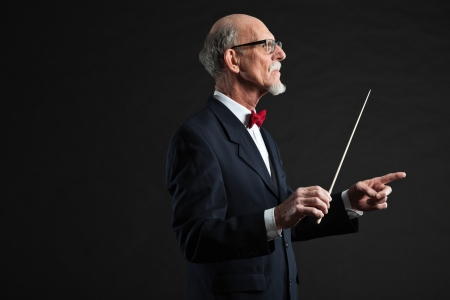 Senior conductor wearing suit. Studio shot.  photo
