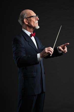 Senior conductor wearing suit. Studio shot. Stock Photo - 19001923