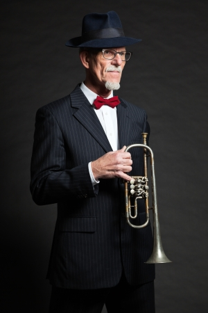 Senior jazz musician. Trumpet player. Studio shot. photo