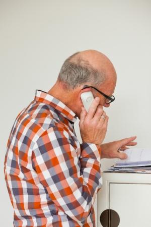 Homem s�nior chamando com telefone port�til na sala de estar. Banco de Imagens