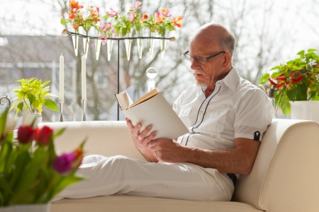 Senior man with glasses reading book in living room. Stock Photo