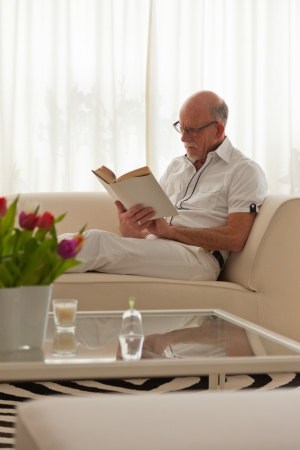 Senior man with glasses reading book in living room. photo