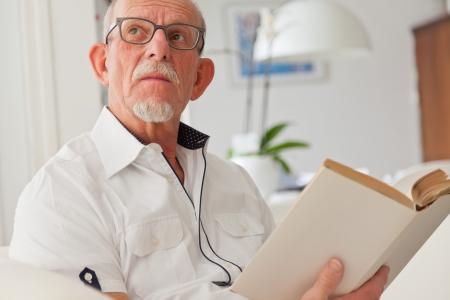 Homem s�nior com vidros livro de leitura na sala de estar.