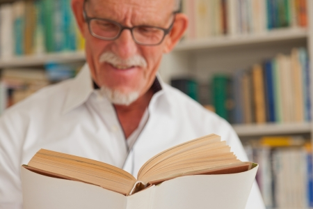 Senior man with glasses reading book in front of bookcase. photo