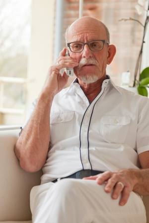 Senior man calling with portable phone in living room. Stock Photo