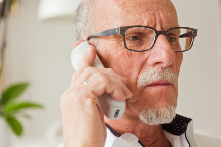 talk to the hand: Senior man calling with portable phone in living room. Stock Photo