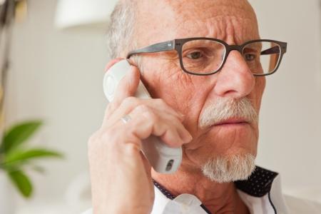 Senior man calling with portable phone in living room. Standard-Bild