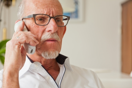 70 year old man: Senior man calling with portable phone in living room. Stock Photo