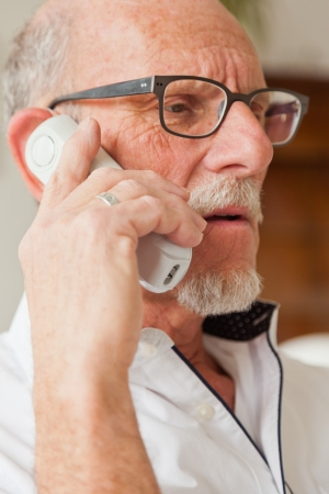 65 70 years: Senior man calling with portable phone in living room. Stock Photo
