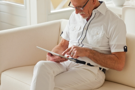 Senior man with glasses using tablet on couch in living room. photo