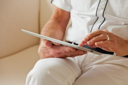 Hands of senior man using tablet. Sitting on white couch. photo