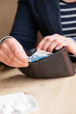 Woman's hands taking money out of wallet. Paying the bill. Stock Photo - 19041215