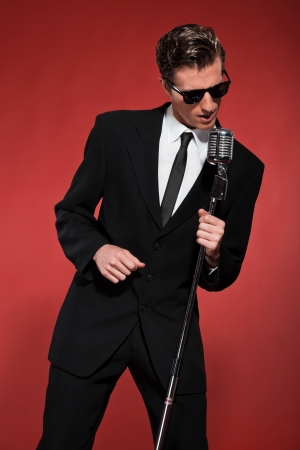 Retro fifties singer with vintage microphone and sunglasses. Studio shot. photo