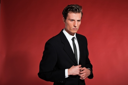 Vintage fifties fashion man with black suit and tie. Studio shot.