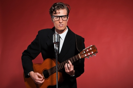 Retro fifties musician with glasses playing acoustic guitar. Studio shot. photo
