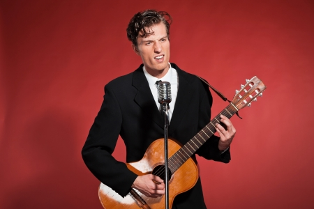 Retro fifties rock and roll singer playing acoustic guitar. Studio shot. photo