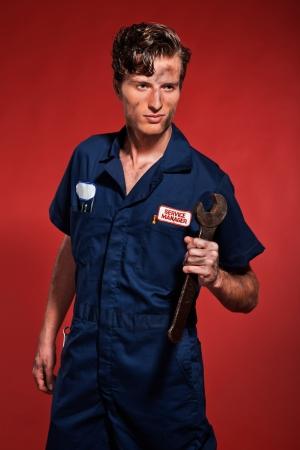 Retro fifties male car mechanic holding tool. Studio shot. photo