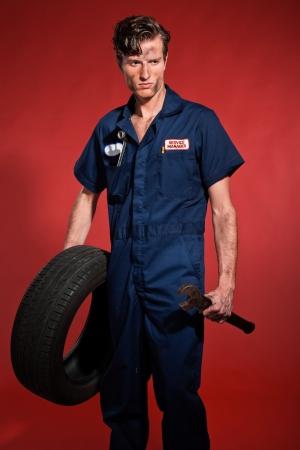 Retro fifties male car mechanic holding tool and tire. Studio shot. photo