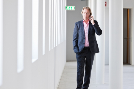 Business man with blue suit walking in white office calling with cellphone. photo