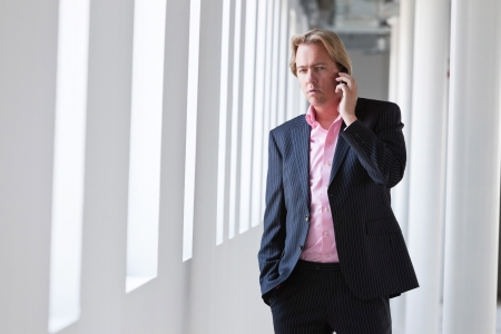 Business man calling with his cellphone in white office. photo