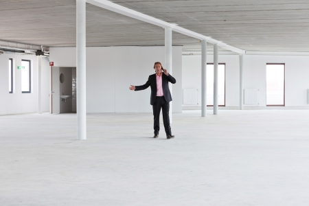moneyless: Business man in crisis walking and calling in empty office.