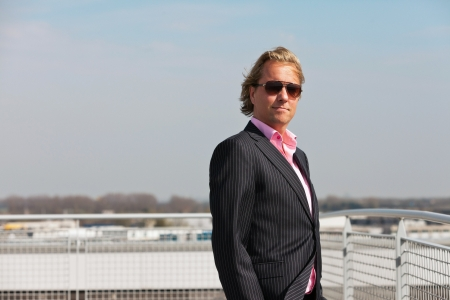 Business man with sunglasses outdoor on rooftop of office building. photo