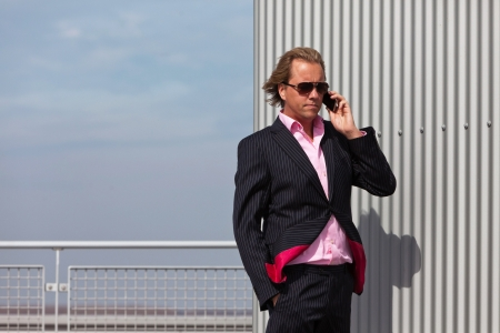 Business man with sunglasses calling near industrial wall. photo