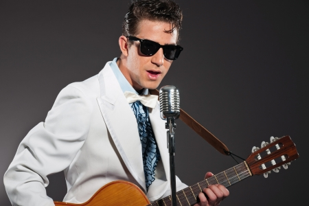 Retro rock and roll singer wearing white suit and black sunglasses photo