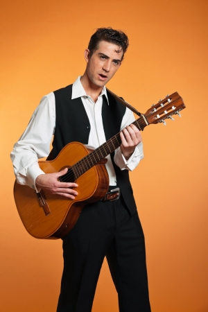 Retro country male guitar player wearing black suit. Studio shot. photo