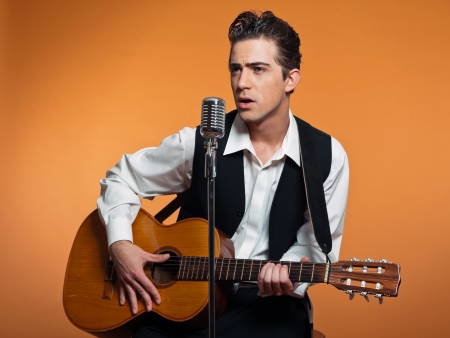 pop singer: Retro country singer with guitar wearing black suit. Studio shot.