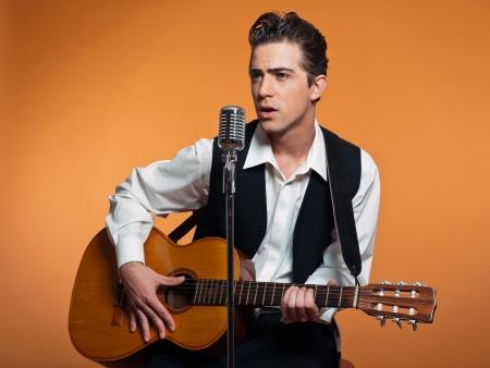 Retro land zanger met gitaar draagt zwarte pak. Studio-opname. Stockfoto